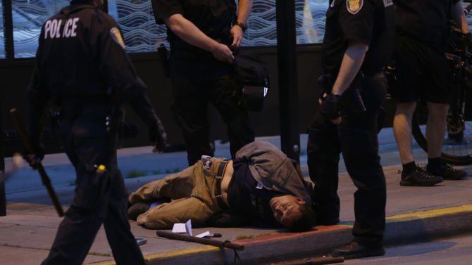 A protester who was arrested during a May Day march that began as an anti-capitalism protest and turned into demonstrators clashing with police lies on the ground next to police batons, Wednesday, May 1, 2013, in downtown Seattle. (AP Photo/Ted S. Warren)