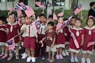 Schoolchildren wave Malaysian flags during the arrival of Britain&#39;s Prince William and his wife Catherine, the Duchess of Cambridge, at the Hospis Malaysia in Kuala Lumpur on September 13. The couple&#39;s marriage in April 2011 was watched by up to two billion TV viewers around the world