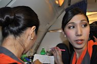 Transsexual fight attendant Phuntakarn Sringern (right) works onboard a Thai PC Air flight between Bangkok and Hong Kong on March 9. Fledgling Thailand-based carrier PC Air has hired four transgender cabin crew in a highly publicised recruitment drive that has divided opinion over whether the move is in the spirit of equality or exploitation