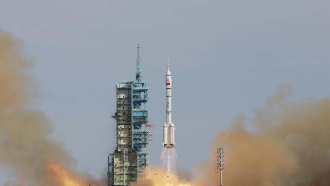 In this photo released by China's Xinhua news agency, the Long March-2F rocket carrying China's manned Shenzhou-10 spacecraft blasts off from the launch pad at the Jiuquan Satellite Launch Center in Jiuquan, northwest China's Gansu Province, Tuesday, June 11, 2013. China's latest manned spacecraft blasted off on a 15-day mission to dock with a space lab. (AP Photo/Xinhua, Li Gang) NO SALES