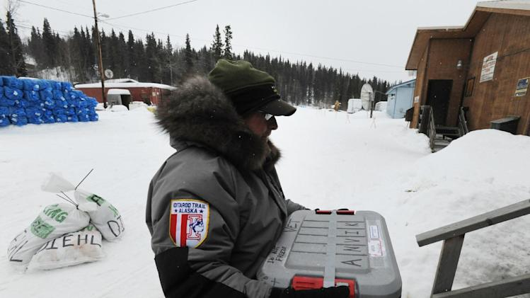 Iditarod veterinarian Mike Hicks carries supplies into the Anvik, Alaska, checkpoint as the Yukon River community anticipates the arrival of the first Iditarod Trail Sled Dog Race mushers Thursday, March 7, 2013. (AP Photo/Anchorage Daily News, Bill Roth)