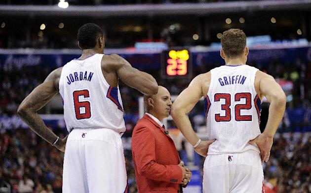 A security guard stands between Los Angeles Clippers' Blake Griffin, right, and DeAndre Jordan during the second half of an NBA basketball game against the Houston Rockets on Monday, Nov. 4, 2013, in