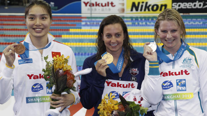 Rebecca Soni, center, of the U.S. shows her gold medal with Australia's Leisel Jones, silver, right, and China's Ji Liping, bronze, during an award ceremony of the women's 100m Breaststoke event at the FINA Swimming World Championships in Shanghai, China, Tuesday, July 26, 2011. (AP Photo/Ng Han Guan)