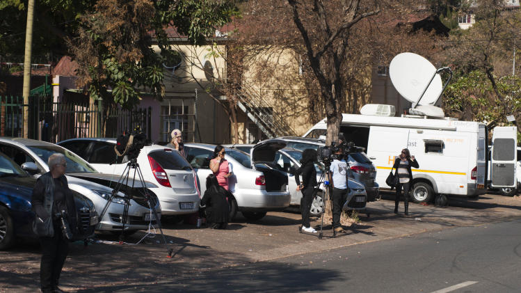 Press gather outisde the hospital, unseen, in Pretoria, South Africa where it is believed that former president Nelson Mandela was hospitalized with a recuring lunch infection early Saturday, June 8, 2013. A presidential statement said that Mandela was in a serious but stable condition. (AP Photo)