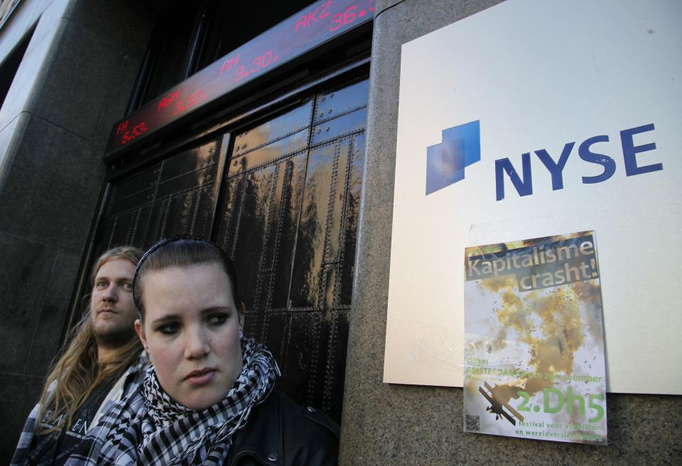 "A woman looks at a flyer reading ""Capitalism Crashes"" attached to the NYSE Euronext stock exchange in Amsterdam, Netherlands, Saturday Oct. 15, 2011, during a demonstration in support of the Occupy Wall Street movement. Demonstrators in hundreds of cities all over the world protested against corporate power and the banking system. (AP Photo/Peter Dejong)"
