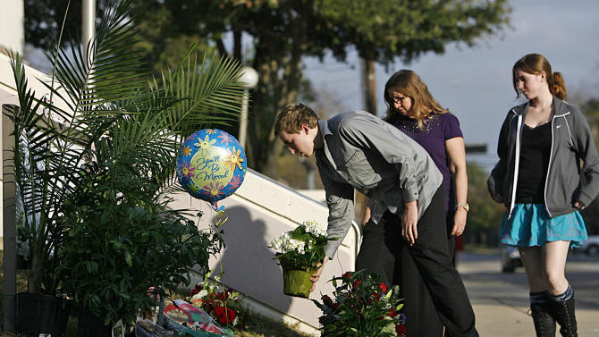 Steven Hester, 18, places flowers next to his sister, Jess, 21, and mother Linda at a memorial for Bellaire Police Cpl. Jimmie Norman outside the Bellaire Police and Courts Building Monday, Dec. 24, 2012, in Houston. A traffic stop turned into a fatal shooting on Christmas Eve when a gunman killed Norman and a bystander in the parking lot of a Houston body shop, police said. (AP Photo/Houston Chronicle, Johnny Hanson)