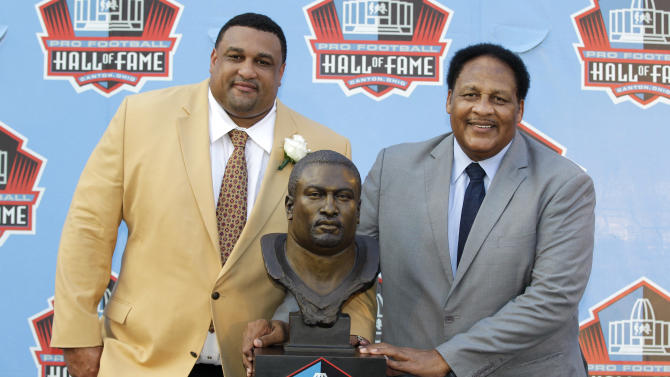 Former NFL player Willie Roaf, left, poses with a bust of himself and his father, Clifton Roaf, during the induction ceremony at the Pro Football Hall of Fame, Saturday, Aug. 4, 2012, in Canton, Ohio. (AP Photo/Gene J. Puskar)