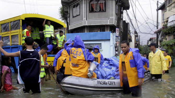 Local government employees push a rubber boat loaded with relief goods Thursday, Aug. 9, 2012 in suburban Pasig City, east of Manila, Philippines. A fresh deluge forced more evacuations along fast-rising rivers in the Philippine capital Thursday, as the city and surrounding areas struggled to deal with widespread flooding triggered by nearly two weeks of relentless rains.  (AP Photo/Pat Roque)