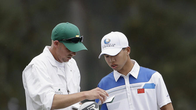 Amateur Guan Tianlang, of China, looks over his course notes with caddie Brian Tam on the first fairway during the first round of the Masters golf tournament Thursday, April 11, 2013, in Augusta, Ga. (AP Photo/Darron Cummings)