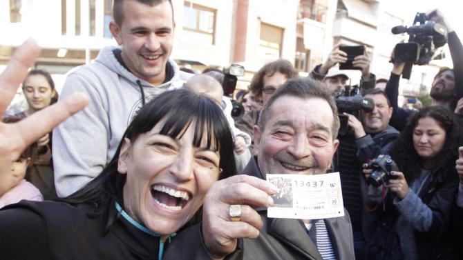 """A man holds his lottery ticket with the winning number of Spain's Christmas Lottery """"El Gordo"""" in La Eliana near Valencia"""