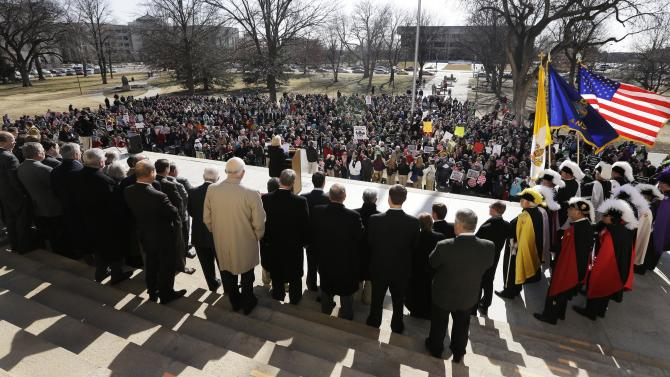 Abortion opponents gather for a rally at the Kansas Statehouse, on the 40th anniversary of Roe v. Wade, in Topeka, Kan., Tuesday, Jan. 22, 2013. Gov. Sam Brownback has signed a series of tough, anti-abortion measures during his first two years in office. Much to the dismay of abortion-rights advocates, Kansas has been part of a wave in which states with Republican governors and GOP-controlled Legislatures enacted new restrictions on abortion providers.  (AP Photo/Orlin Wagner)