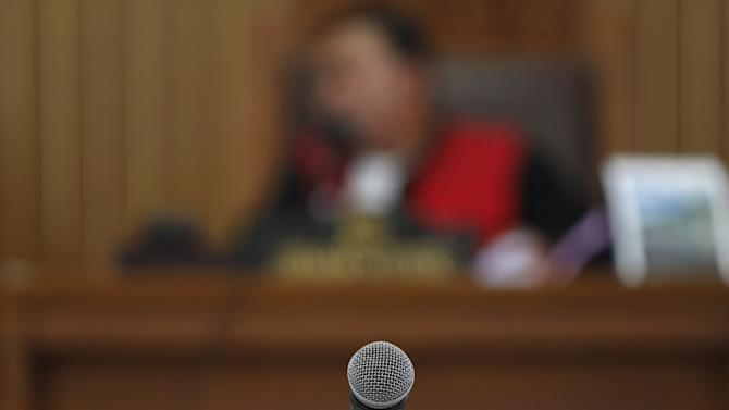 A judge is seen in the background of a microphone, as convicted Indonesian muslim cleric Abu Bakar Bashir did not attend a hearing for his appeal against a 15-year jail term, at a district court in South Jakarta