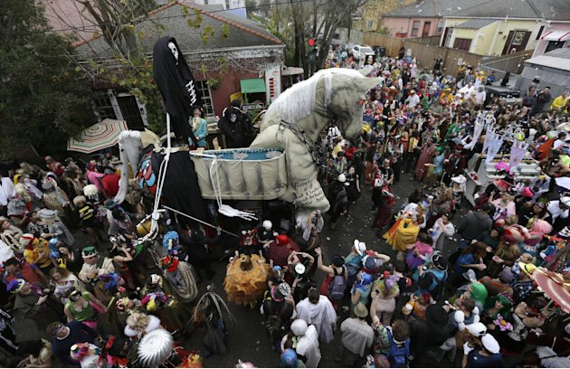 A trojan horse float makes its way through the crowd as revelers gather for the start of the Society of Saint Anne walking parade in the Bywater section of New Orleans during Mardi Gras day, Tuesday,