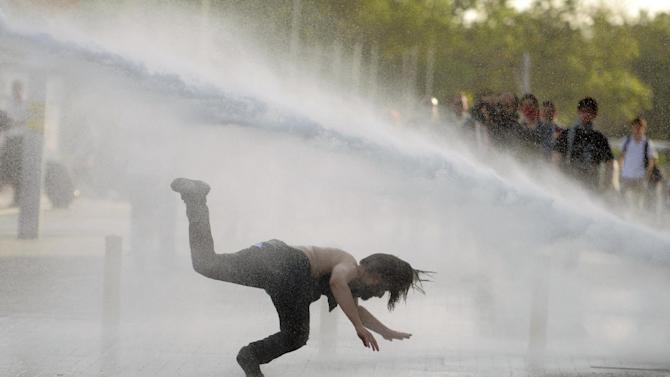 A man falls as riot police use tear gas and pressurized water to quash a peaceful demonstration by hundreds of people staging a sit-in protest to try and prevent the demolition of trees at an Istanbul park, Turkey, Friday, May 31, 2013. A number of protesters were injured. Police moved in at dawn Friday to disperse the crowd on the fourth day of the protest against a contentious government plan to revamp Istanbul's main square, Taksim. The protesters are demanding that the square's park, Gezi, is protected. (AP Photo)