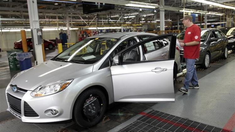 A Ford Motor assembly worker inspects the new 2012 Ford Focus vehicles on the final production line at Michigan Assembly Plant in Wayne