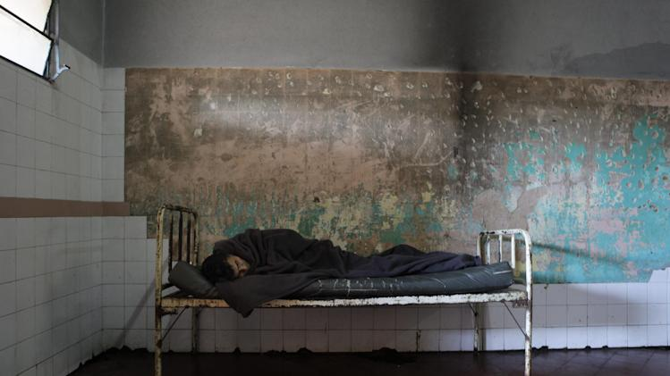 In this May 29, 2013 photo, a patient sleeps in a bedroom at the Neuro-Psychiatric Hospital in Asuncion, Paraguay. Paraguay's only public psychiatric hospital has no money for heating to protect patients from the biting chill during the winter months. (AP Photo/Jorge Saenz)