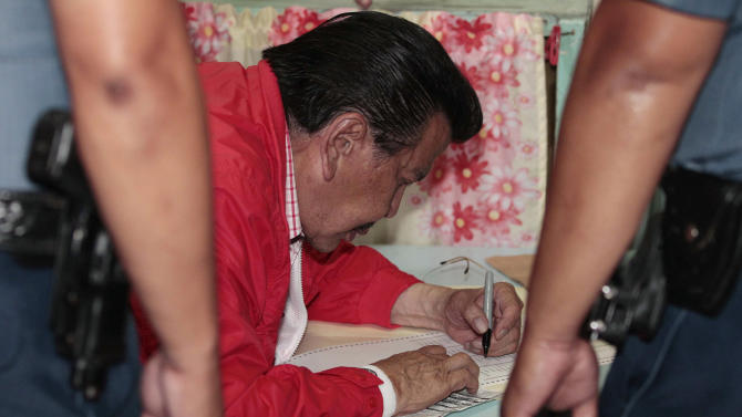 Former Philippine President Joseph Estrada, who is running for mayor of Manila, fills out a ballot inside a classroom used as a voting precinct during mid-term elections in Manila, Philippines on Monday, May 13, 2013. The country is electing local officials from senators to congressmen and down to municipal mayors during Monday's mid-term elections. (AP Photo/Aaron Favila)