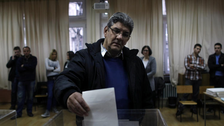 A man casts his ballot inside a polling station in Belgrade, Serbia, Sunday, March 16, 2014. Polls have opened at the parliamentary elections in Serbia on Sunday, with the ruling Serbian Progressive Party seen as a clear favorite to win the majority of votes. (AP Photo/Marko Drobnjakovic)