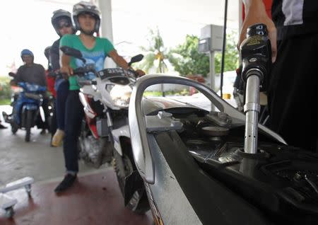 An employee of state-owned Pertamina refuels a motorcycle at its petrol station in Jakarta