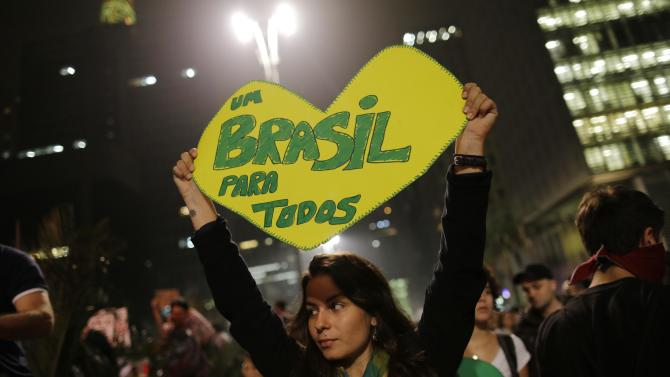"A woman holds up a heart-shaped sign that reads in Portuguese ""One Brazil for all,"" on Paulista Avenue where crowds gathered to celebrate the reversal of a fare hike on public transportation, in Sao Paulo, Brazil, Thursday, June 20, 2013. President Dilma Rousseff called an emergency meeting of her top Cabinet members for Friday morning, more than a week after the protests began. Rousseff, who has a standoffish governing style, has been almost entirely absent from the public eye, making only one statement earlier in the week that peaceful protests are part of the democratic process. (AP Photo/Nelson Antoine)"