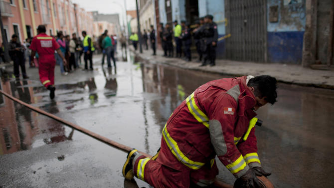 In this Nov. 4, 2012 photo, a firefighter rolls up a hose after a fire destroyed an old building in Lima, Peru. Seismologists, engineers and civil defense officials agree that Lima is due for an earthquake but is acutely vulnerable and sorely unprepared. Only Lima's 4,000 firefighters, all volunteers, have comprehensive first-aid training, as does a 1,000-officer police emergency squadron. Water is also a worry. The fire threat to Lima is severe, to refineries and to densely-backed neighborhoods honeycombed with colonial-era wood and adobe. Lima's firefighters often can't get enough water pressure to douse a blaze. (AP Photo/Rodrigo Abd)