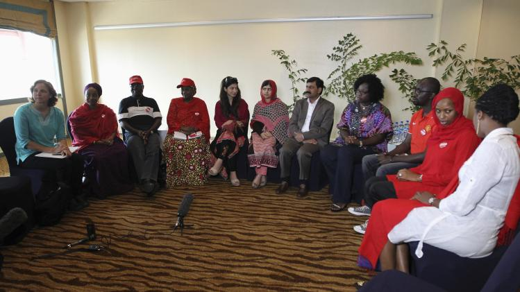 Pakistani schoolgirl activist Malala Yousafzai sits with her father Ziauddin Yousafzai and Malala Fund CEO Shiza Shahid during a meeting with the leaders of the #BringBackOurGirls Abuja campaign group, in Abuja