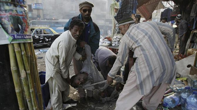 Pakistani volunteers carry a wounded passenger following a blast in Karachi, Pakistan on Saturday, Dec. 29, 2012. The blast that ripped through the bus  set the vehicle on fire and reduced it to little more than a charred skeleton, killing scores of people and left many injured. Police were trying to determine whether the explosion was caused by a bomb or a gas cylinder, said police spokesman. Many buses in Pakistan run on natural gas. (AP Photo/Fareed Khan)