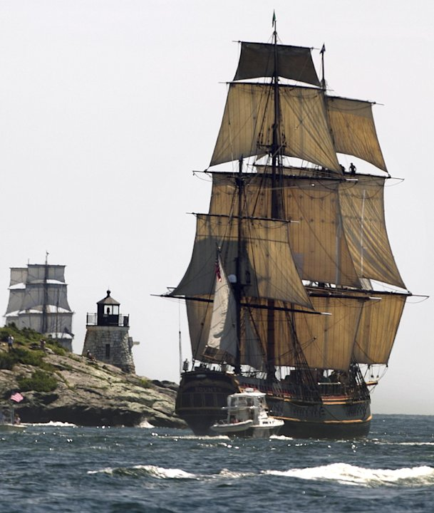 FILE - In this July 9, 2012, file photo, a replica of the historic ship HMS Bounty, right, sails past a lighthouse, center, as it departs Narragansett Bay and heads out to sea off the coast of Newport