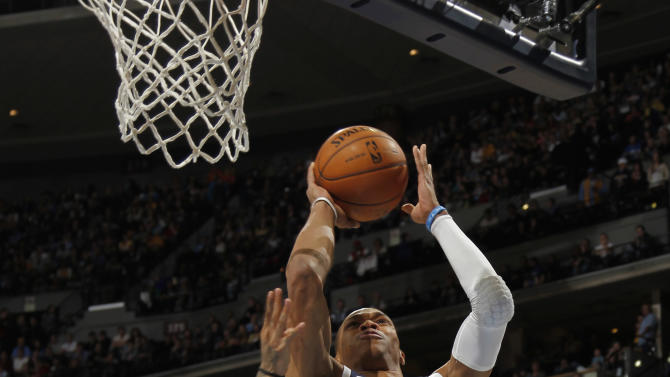 Oklahoma City Thunder guard Russelll Westbrook, right, goes up for a shot past Denver Nuggets forward Wilson Chandler, left, and center Kosta Koufos in the first quarter of an NBA basketball game in Denver on Friday, March 1, 2013. (AP Photo/David Zalubowski)