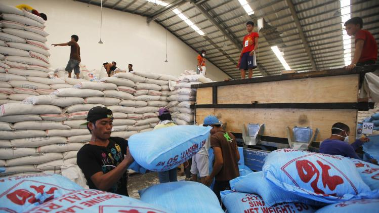 Workers prepare rice for distribution at a relief center during U.S. Secretary of State Kerry's tour of the damage from super typhoon Haiyan in Tacloban