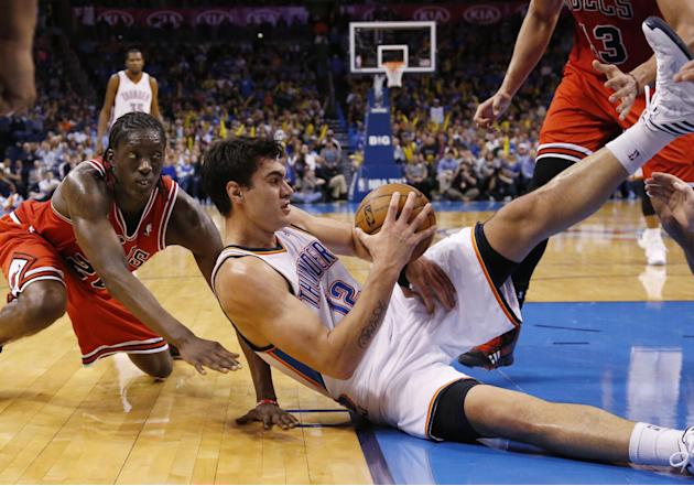 Oklahoma City Thunder center Steven Adams (12) keeps the ball away from Chicago Bulls forward Tony Snell, left, during the fourth quarter of an NBA basketball game in Oklahoma City, Thursday, Dec. 19,