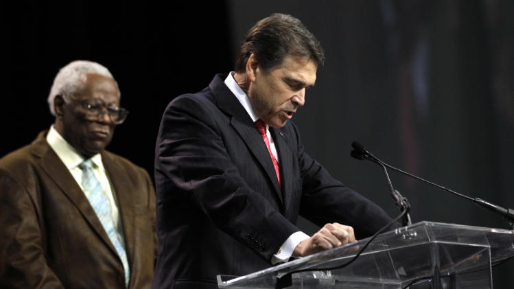 FILE - In this Aug. 6, 2011, file photo Texas Gov. Rick Perry, right, joined on stage by Pastor C.L. Jackson, bows his head in prayer at The Response, a call to prayer for a nation in crisis in Houston. During the prayer rally for thousands Perry read from the Bible, invoked Christ, and broadcast the whole event on the Web, without so much as a symbolic nod to other American faiths. It was a rare, full-on embrace of one religious tradition in the glare of a presidential contest. (AP Photo/David J. Phillip, File)