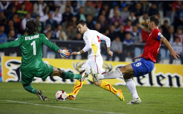 Macedonia's Jahovic scores a goal against Serbia's goalkeeper Stojkovic during their 2014 World Cup qualifying soccer match in Jagodina