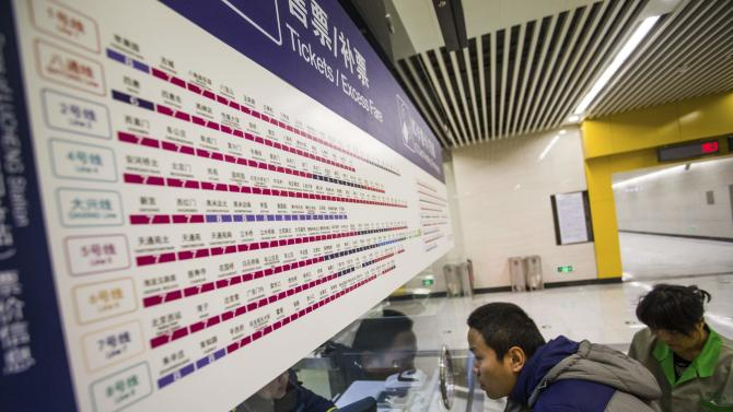 A passenger talks to a clerk under a board showing the new prices of Beijing subway lines at a subway station in Beijing