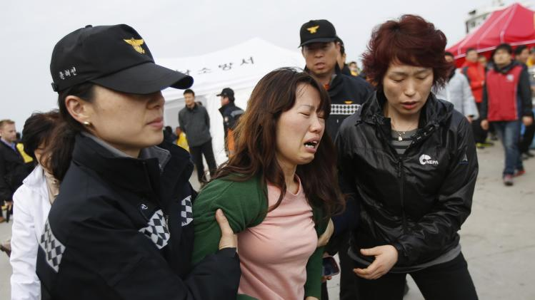 A family member of missing passengers who were on the South Korean ferry Sewol which sank in the sea off Jindo, cries as she found the name of her family in the list of fatalities at a port, in Jindo