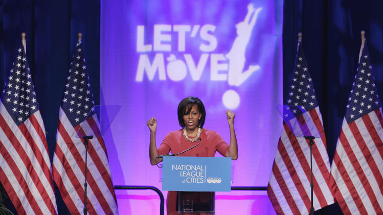 """FILE - In this March 15, 2011, file photo, first lady Michelle Obama gestures while speaking speaks at the National League of Cities Conference about the Let's Move! initiative in Washington. Michelle Obama has a new look, both in person and online, and with the president's re-election, she has four more years as first lady, too. The first lady is trying to figure out what comes next for this self-described """"mom in chief"""" who also is a champion of healthier eating, an advocate for military families, a fitness buff and the best-selling author of a book about her White House garden. For certain, she'll press ahead with her well-publicized efforts to reduce childhood obesity and rally the country around its service members. (AP Photo/File)"""