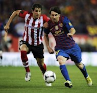 Athletic Bilbao&#39;s defender Borja Ekiza (L) clashes with Barcelona&#39;s forward Lionel Messi during the Spanish King&#39;s Cup final football match at the Vicente Calderon stadium, in Madrid. Barcelona won 3-0