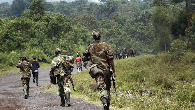 A column  of Congolese  M23 rebels   is seen running on the Goma to Rushuru road as they  look for FDLR (Force Democratique de Liberation du Rwanda) returning from an incursion into Rwanda Near Kibumba, north of Goma Tuesday Nov. 27, 2012. Speaking in Goma , M23 president Jean Marie Runiga said the rebels will not leave the city of 1 million which they seized a week ago. Rwanda military spokesman confirmed FDLR attacked Rwandan positions on Tuesday, which they repulsed and send back to Congo. (AP Photo/Jerome Delay)