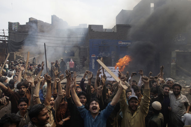 "An angry mob reacts after burning Christian houses in Lahore, Pakistan, Saturday, March 9, 2013. A mob of hundreds of people in the eastern Pakistani city of Lahore attacked a Christian neighborhood Saturday and set fire to homes after hearing accusations that a Christian man had committed blasphemy against Islam's prophet Mohammed, said a police officer. Placard center reads, "" Blasphemer is liable to death."" (AP Photo/K.M. Chaudary)"
