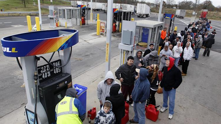 People line up to fill gas containers at the New Jersey Turnpike's Thomas A. Edison service area Wednesday, Oct. 31, 2012, near Woodbridge, N.J. The price of oil is rising as operations at refineries and supply terminals in the Northeast remain restricted three days after Superstorm Sandy. Benchmark oil gained 60 cents Thursday to $86.84 per barrel in New York.  (AP Photo/Mel Evans)