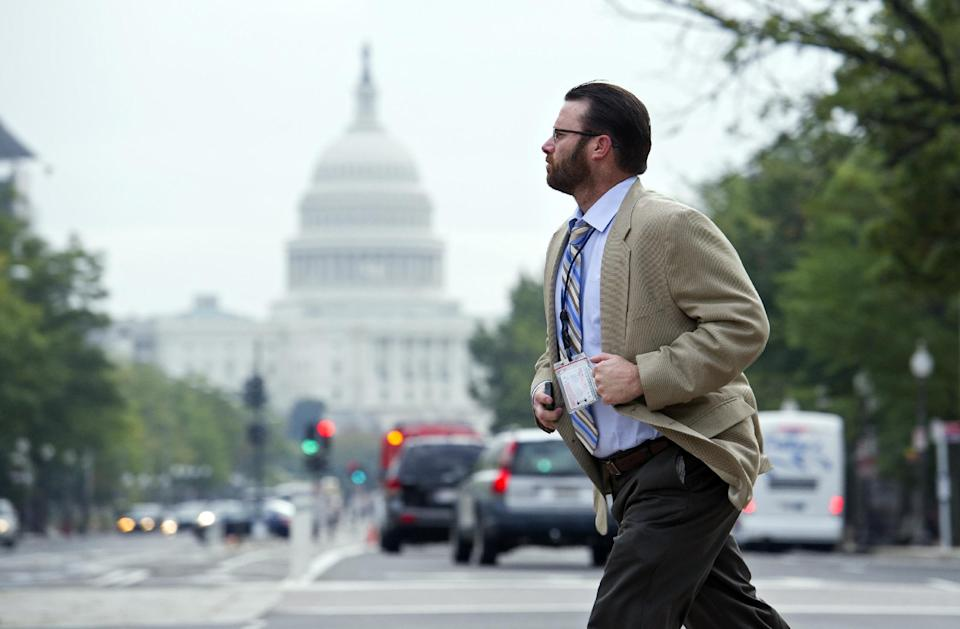 A man crosses Pennsylvania Ave., NW, in front of the Justice Department, in Washington, Thursday, Oct. 17, 2013. After 16 days of being off the job, thousands of furloughed federal workers are returning to work now that the government shutdown has been resolved. (AP Photo/Cliff Owen)