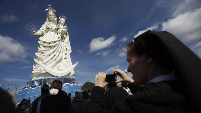 "A nun takes pictures of a newly unveiled statue of the Virgin Mary holding a baby Jesus on Santa Barbara hill in the mining city of Oruro, Bolivia, Friday, Feb. 1, 2013. The 45 meter (147 feet) statue that took four years to build, known in Spanish as ""Virgen del Socavón,"" or the Virgin of the Tunnel, is Oruro's patron, venerated in particular by miners and folkloric Carnival dancers. (AP Photo/Juan Karita)"