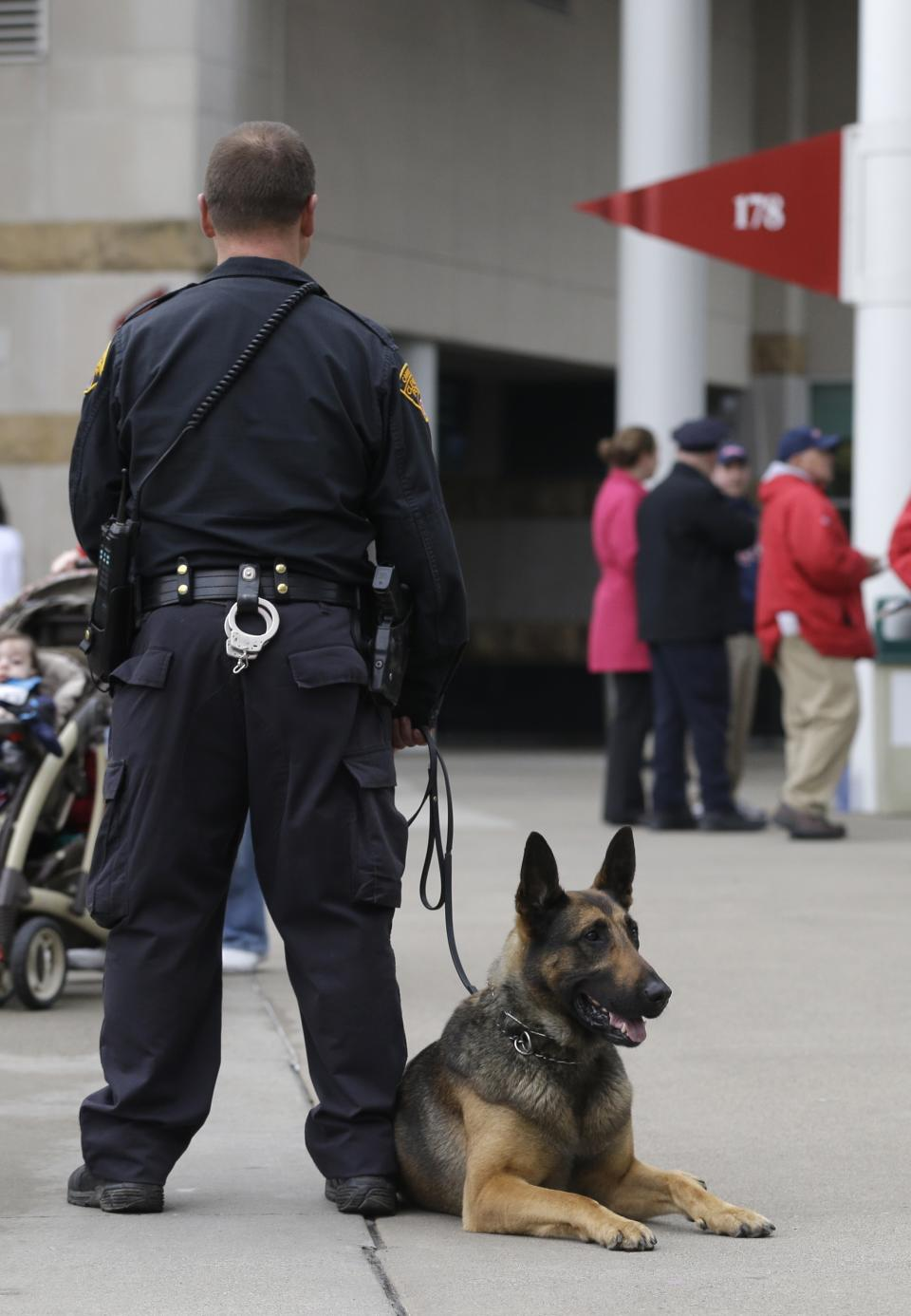A Cleveland police K-9 unit patrols inside a gate at Progressive Field before a baseball game between the Boston Red Sox and Cleveland Indians Tuesday, April 16, 2013, in Cleveland. (AP Photo/Mark Duncan)