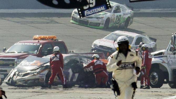 FILE - In this March 24, 2013, file photo, rescue workers tend to the wreckage of Denny Hamlin (11) after he collided with Joey Logano on the final lap of the NASCAR Sprint Cup series auto race in Fontana, Calif. NASCAR is not penalizing Tony Stewart for scuffling with Joey Logano on pit road at California, and viewed the crash between Logano and Denny Hamlin as a racing incident.  (AP Photo/Reed Saxon, File)