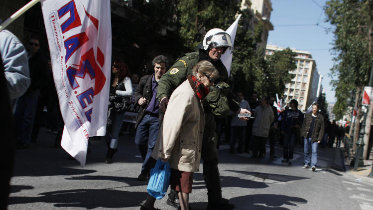 A police officer helps an elderly woman to cross the street during a protest by the pro-communist union PAME in Athens, Wednesday, Feb. 20, 2013. Thousands of anti-austerity demonstrators took to the streets of Athens on Wednesday as unions staged a general strike to protest the government's spending cuts and tax hikes, which some predict will push unemployment to a stunning 30 percent this year. (AP Photo/Kostas Tsironis)