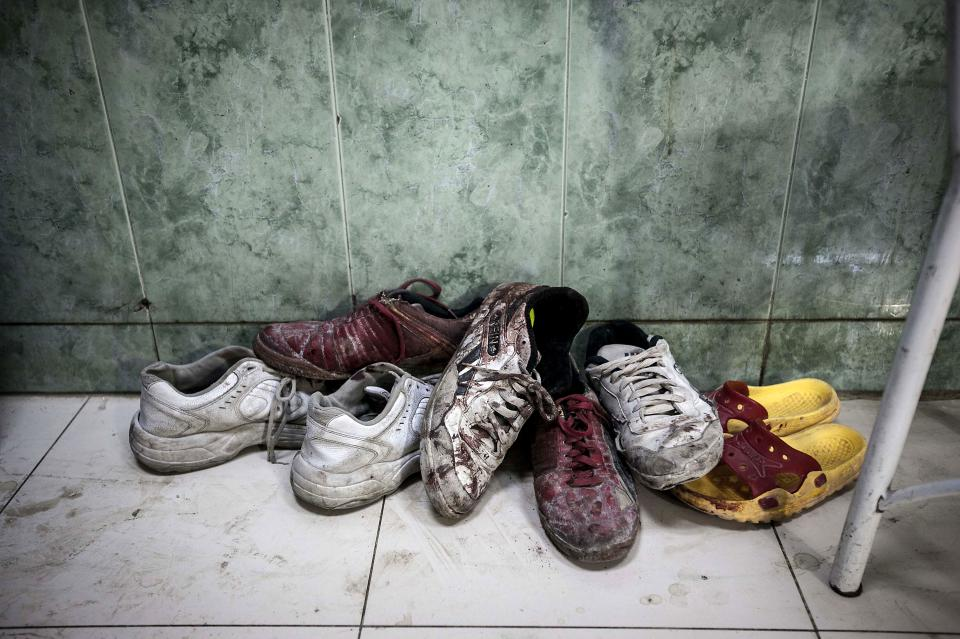 In this Thursday, Nov. 1, 2012 photo, a pile of shoes covered by blood from wounded or dead residents lies at the entrance of the emergency ward at a hospital in the Tarik Al-Bab neighborhood in Aleppo, Syria. (AP Photo/Narciso Contreras)