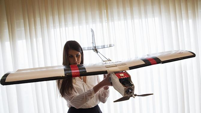 In this photo taken Jan. 20, 2015 file photo, Lia Reich, director of marketing with PrecisionHawk, holds up their agricultural and insurance drone, the PrecisionHawk Lancaster, after an event with the Small Unmanned Aerial Vehicles (UAV) Coalition, at the National Press Club in Washington. Farmers and ranchers are eagerly awaiting the ability to use drones commercially on their land _ technology that could have benefits for consumers, too. Unmanned aircraft could make farmers more efficient by helping them locate problem spots in vast fields or ranchlands. It could mean less impact on the environment, if farmers used fewer chemicals because drones showed them exactly where to spray. Five ways drones could impact the food supply. (AP Photo/Jacquelyn Martin)