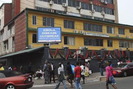 """Pedestrians walk past a sign reading """"Ebola disease outbreak"""" outside the Ministry of Finance in Monrovia"""