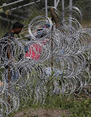 People try to cross under a wire fence on the Serbian…