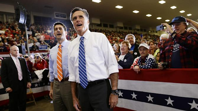 Republican presidential candidate and former Massachusetts Gov. Mitt Romney and vice presidential candidate Rep. Paul Ryan, R-Wis., look up towards the stage and sing along with The Oak Ridge Boys as they campaign at the Veterans Memorial Coliseum, Marion County Fairgrounds, in Marion, Ohio, Sunday, Oct. 28, 2012. (AP Photo/Charles Dharapak)
